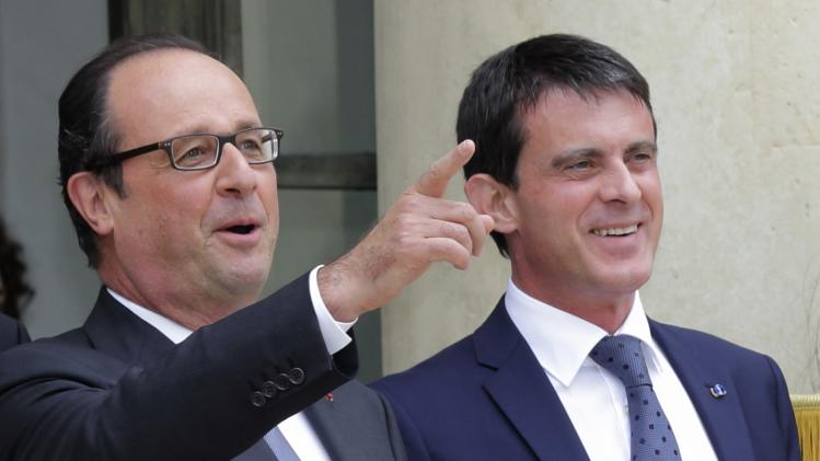 French President Francois Hollande and Prime Minister Manuel Valls speak together at the Elysee Palace in Paris