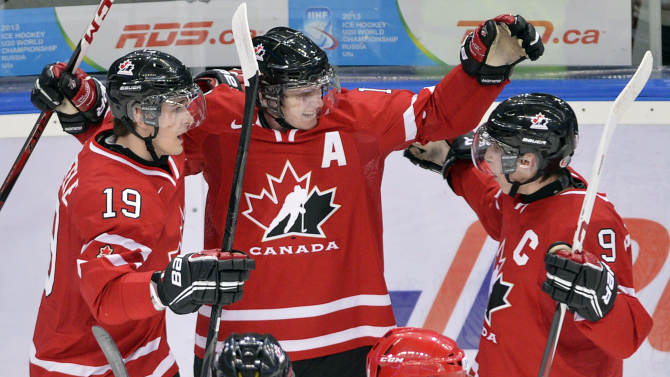 Canada's Jonathan Huberdeau, center, celebrates his goal with teammates Mark Scheifele, left, and Ryan Nugent-Hopkins as they face Russia during the first period of the bronze medal hockey game at the IIHF World Junior Championships, Saturday, Jan. 5, 2013, in Ufa, Russia. (AP Photo/The Canadian Press, Nathan Denette)