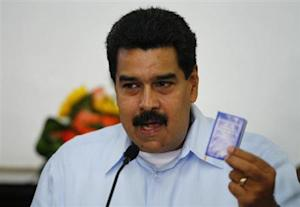 Venezuela's President Maduro holds a copy of the country's constitution during a news conference in Caracas