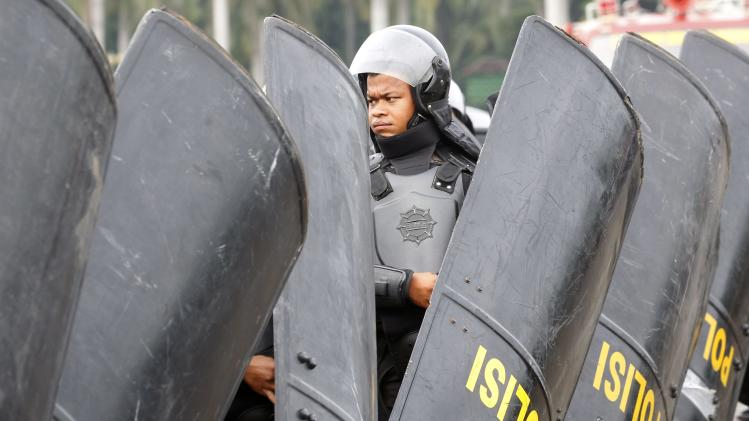 A member of the Indonesian National Police carries his riot gear in preparation for a security operation in Jakarta