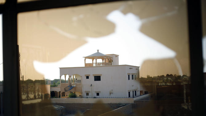 In sharp contrast with most mud homes  found in Gao, a luxury house  once occupied by  reputed drug traffickers turned finance operatives for rebel jihadists   seen through a broken window in Gao, northern Mali, Monday Feb. 18, 2013. (AP Photo/Jerome Delay)