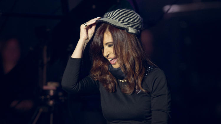 "Argentina's President Cristina Fernandez tries on a hat given to her by a supporter at a government event outside the government house in Buenos Aires, Argentina, Saturday, May 25, 2013.  Fernandez's government and supporters are celebrating 10 years since she and her late husband have held office, and the 203th anniversary of the Argentina's May Revolution. This year's election will determine whether she has the votes in congress to undo constitutional term limits and extend her rule beyond 2015. But she suggested Saturday night that she won't try. She said ""I'm not eternal, nor do I want to be."" (AP Photo/Natacha Pisarenko)"