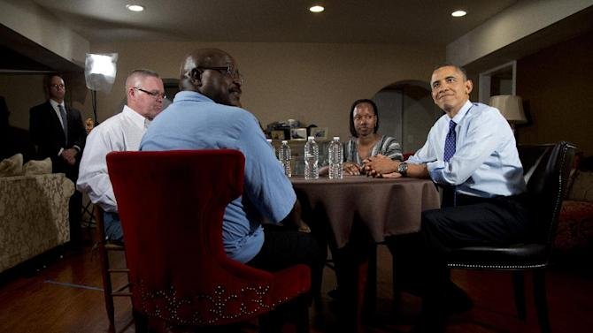 President Barack Obama listens while speaking to the media during a visit with high school teacher Tiffany Santana, second from right, Tiffany's mother Velma Massenburg, third from right, obscured, Tiffany's father Jimmy Massenburg center, and Richard Santana, who works at a local Toyota dealership, left, Thursday, Dec. 6, 2012, in Falls Church, Va., to discuss the importance of extending income tax cuts for Americans and small businesses. (AP Photo/Carolyn Kaster)