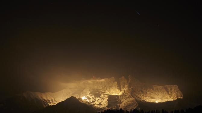 A meteor streaks above the Dents-du-Midi mountain being artificially lit during the 13 Summits event in Champoussin