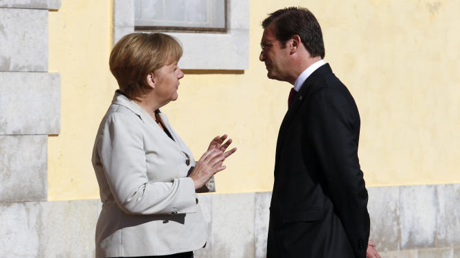 Germany's Chancellor Angela Merkel, left, talks with Portugal's Prime Minister Pedro Passos Coelho before their meeting at the Sao Juliao da Barra fort in Oeiras, Portugal, Monday, Nov. 12, 2012. Merkel was Monday making another trip to a bailed-out eurozone country where many people blame her government for the harsh austerity measures they are enduring. Merkel was due to pay a brief visit to Portugal, which needed a euro 78 billion ($99 billion) rescue last year, in what was widely seen as a display of support for the Portuguese government's efforts to restore the country's fiscal health in the teeth of broad public and political opposition. (AP Photo/Francisco Seco)