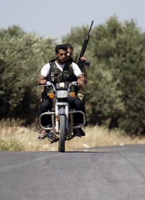 Armed Free Syrian Army soldiers ride a motorcycle on the outskirts of Idlib, Syria, Sunday, June 3, 2011. Free Syrian Army soldiers are determined to bring down the regime by force of arms, targeting military checkpoints and other government sites. A U.N. observer team with nearly 300 members has done little to quell the bloodshed. (AP Photo)