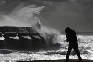 A man watches stormy seas in strong winds as waves crash on the harbour wall at Brighton marina in south east England