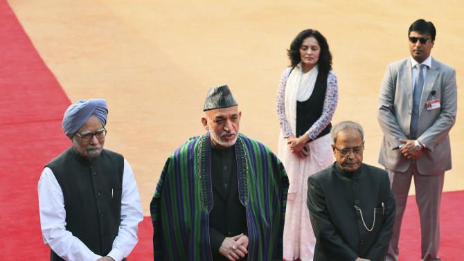 Afghanistan's President Hamid Karzai, center, stands with Indian Prime Minister Manmohan Singh, left, and President Pranab Mukherjee during a ceremonial reception at the Presidential Palace in New Delhi, India, Monday, Nov. 12, 2012. Karzai is on a four-day official visit to India. (AP Photo/Manish Swarup)