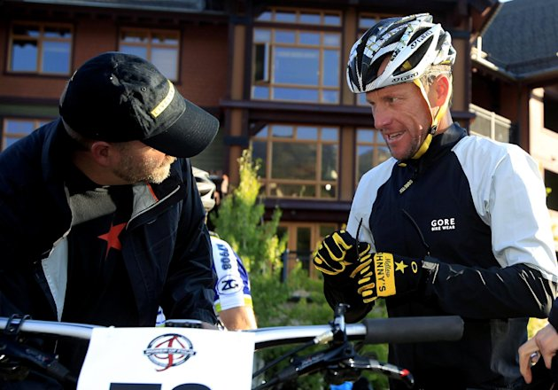 Lance Armstrong, center, prepares to take part in the Power of Four mountain bicycle race at the starting line in Snowmass Village, Colo., early Saturday, Aug. 25, 2012. The race is the first public a