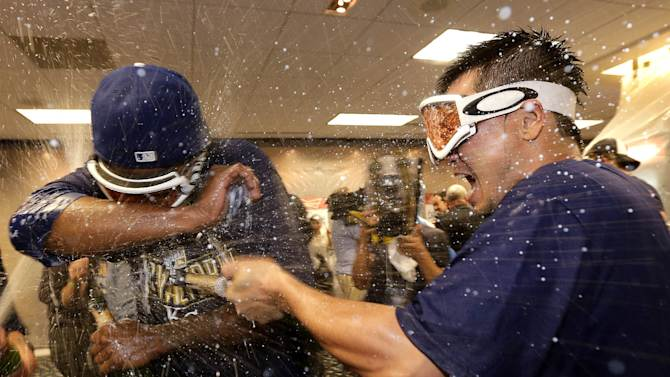 Kansas City Royals pitcher Yordano Ventura, left, and right fielder Norichika Aoki, right, celebrate in the clubhouse after the Royals' 9-8 win in 12 innings in the AL wild-card playoff baseball game against the Oakland Athletics, early Wednesday, Oct. 1, 2014, in Kansas City, Mo. (AP Photo/Charlie Riedel)