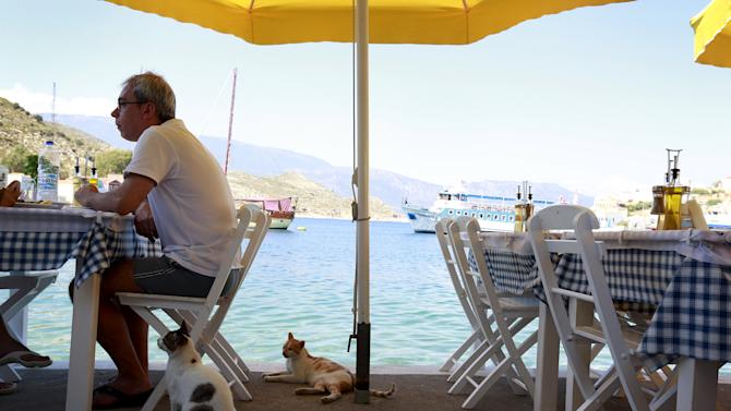 Cats wait for scraps of food at a restaurant in the village of Meyisti on the Island of Kastellorizo which is the most easterly of the islands in Greece