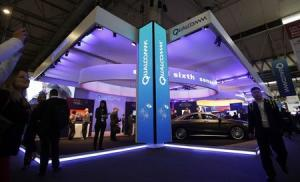 File photo of visitors walking past the Qualcomm stand at the Mobile World Congress in Barcelona