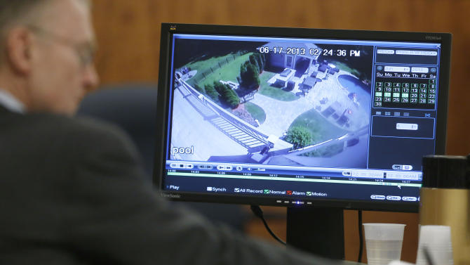 Charles Rankin, left, defense attorney for former New England Patriots football player Aaron Hernandez, uses a pen as a June 17, 2013 surveillance video from Hernandez's home is displayed on a monitor during Hernandez's murder trial Thursday, March 26, 2015, in Fall River, Mass. Hernandez is charged with killing Odin Lloyd in June 2013. (AP Photo/Steven Senne, Pool)