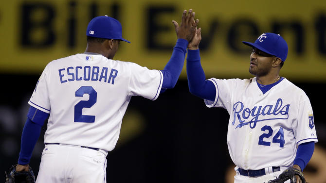 Kansas City Royals shortstop Alcides Escobar (2) celebrates with second baseman Christian Colon (24) following a baseball game against the Minnesota Twins at Kauffman Stadium in Kansas City, Mo., Monday, April 20, 2015. The Royals defeated the Twins 7-1. (AP Photo/Orlin Wagner)