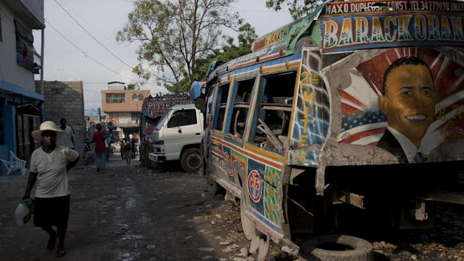 A woman walks past a damaged bus with an image depicting President Barack Obama in Port-au-Prince, Haiti, Wednesday Nov. 7, 2012. Obama was re-elected for a second presidential term, defeating his Republican challenger, former Massachusetts Gov. Mitt Romney in Tuesday's election. (AP Photo/Dieu Nalio Chery)