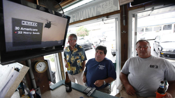 Virginia Beach residents Tom Hall, left, and Mark Janik, center, watch as news about the Navy Seal Team Six helicopter accident is displayed on a television at a bar in Virginia Beach , Va., Saturday, Aug. 6, 2011. The headquarters for the Navy Seal Team Six is located in Virgina Beach. (AP Photo/Steve Helber)