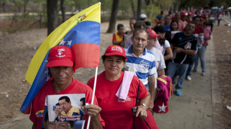 People queue outside the military academy where Venezuela's late President Hugo Chavez is lying in state in Caracas, Venezuela, Sunday, March 10, 2013. Chavez died on March 5 after a nearly two-year bout with cancer. He was 58. (AP Photo/Ariana Cubillos)