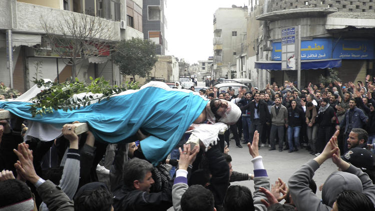 People carry the body of Mohammed al-Mnawi who was allegedly killed by the Syrian security forces on Saturday as they shout anti-government slogans during his funeral in Kfar Suseh area, Damascus, Syria, Tuesday, Feb. 28, 2012. (AP Photo)