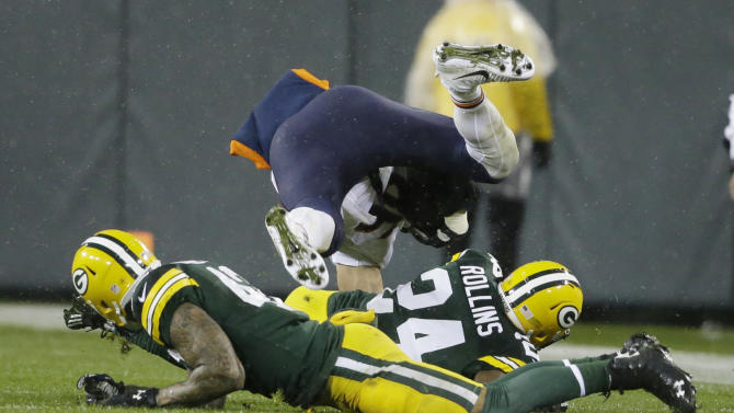 Chicago Bears' Zach Miller is tripped up by Green Bay Packers' Morgan Burnett and Quinten Rollins (24) during the second half of an NFL football game Thursday, Nov. 26, 2015, in Green Bay, Wis. (AP Photo/Jeffrey Phelps)