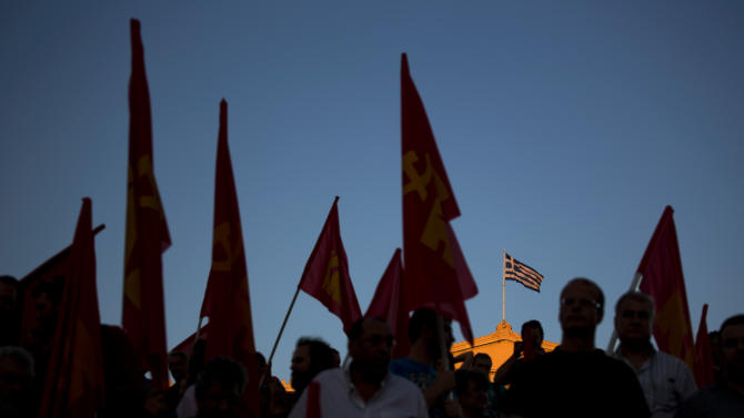 A Greek flag flies atop the parliament building as demonstrators from the Greek Communist party gather during a rally supporting the no vote for the upcoming referendum in Athens, Thursday, July 2, 2015. The battle for Greek votes entered full swing Thursday ahead of a crucial weekend referendum that could decide whether the country falls out of the euro. (AP Photo/Emilio Morenatti)
