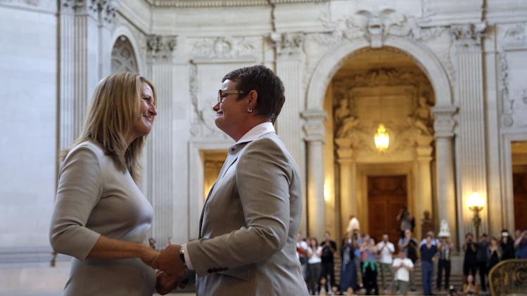 Sandy Stier, left, exchanges wedding vows with Kris Perry during a ceremony presided by California Attorney General Kamala Harris at City Hall in San Francisco, Friday, June 28, 2013. Stier and Perry, the lead plaintiffs in the U.S. Supreme Court case that overturned California's same-sex marriage ban, tied the knot about an hour after a federal appeals court freed same-sex couples to obtain marriage licenses for the first time in 4 1/2 years. (AP Photo/Marcio Jose Sanchez)