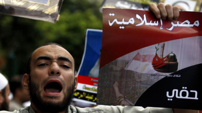 """FILE - In this Friday, Sept. 23, 2011 file photo, an Egyptian man chants slogans and holds a poster that reads, in Arabic, """"Islamic Egypt,"""" during a demonstration held by a Salafi group to protest the emergency law, in Tahrir Square in Cairo, Egypt. Under Mubarak, there were no mass killings along the lines of South African or some Latin American dictatorships in the 1980s. But tens of thousands of political prisoners were detained under emergency laws that expired last week after 31 years in force. Torture was systematic, and often extreme, and corruption was completely endemic. (AP Photo/Khalil Hamra, File)"""