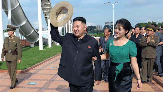 ADDS DATE - In this Wednesday, July 25, 2012 photo released by the Korean Central News Agency (KCNA) and distributed in Tokyo by the Korea News Service Thursday, July 26, 2012, North Korean leader Kim Jong Un, center, accompanied by his wife Ri Sol Ju, right, waves to the crowd as they inspect the Rungna People's Pleasure Ground in Pyongyang. (AP Photo/Korean Central News Agency via Korea News Service) JAPAN OUT UNTIL 14 DAYS AFTER THE DAY OF TRANSMISSION
