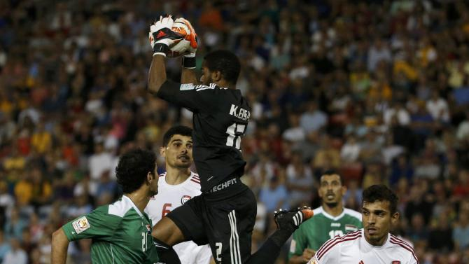 UAE's goalkeeper Khalid Eisa jumps to make a save between team mate Walid Abbas and Iraq's Saad Abdulameer Al-Dobjahawe during their Asian Cup third-place playoff soccer match at the Newcastle Stadium in Newcastle