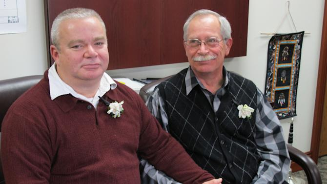 Tim LaCroix, left, and Gene Barfield relax in the tribal chairman's office, Friday, March 15, 2013, in Harbor Springs, Mich., after becoming the first gay couple wed under a newly approved measure allowing same-sex marriage for members of the Little Traverse Bay Bands of Odawa Indians in Michigan. (AP Photo/John Flesher)