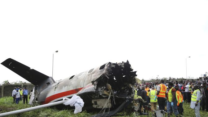 Rescue workers stand near the tail of a plane at the site of a plane crash near the Lagos international airport