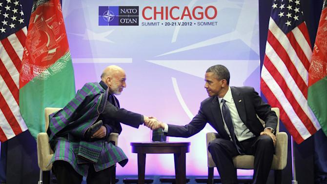 FILE - In this May 20, 2012, file photo, President Barack Obama, right, shakes hands with with Afghan President Hamid Karzai, left, during their meeting at the NATO Summit in Chicago. The Obama administration gave the first explicit signal Tuesday, Jan. 8, 2013, that it might leave no troops in Afghanistan after December 2014, an option that defies the Pentagon's view that thousands of troops may be needed to keep a lid on al-Qaida and to strengthen Afghan forces. Karzai is scheduled to meet with Obama at the White House on Friday. (AP Photo/Pablo Martinez Monsivais, File)