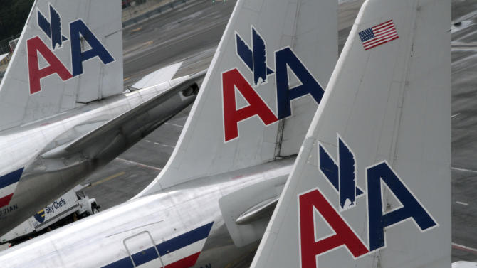 FILE - In this Wednesday, Aug. 1 2012 file photo, American Airlines airplanes are parked at their gates at JFK International airport in New York. American Airlines said Wednesday, Oct. 17, 2012 said that it will post job openings for 1,500 flight attendants next month. It will start hiring in December and put the new staff in training beginning in January. (AP Photo/Mary Altaffer, File)