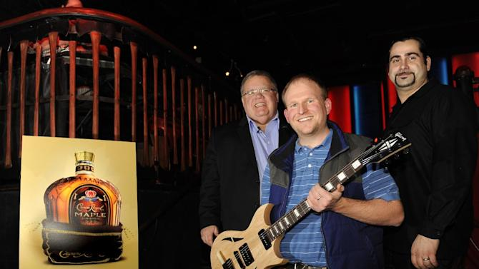 IMAGE DISTRIBUTED FOR CROWN ROYAL - Master of Whisky Steve Beal, left, and mixologist Alex Straus, right, award Lloyd Reese with a Maple Finished Gibson guitar at the Crown Royal Maple Finished Denver Launch party at Double Daughters Salotto, Tuesday, Jan. 22, 2013, in Denver. Reese won the guitar for mixing the best Crown Royal Maple Finished cocktail. (Jack Dempsey/AP Images for Crown Royal)