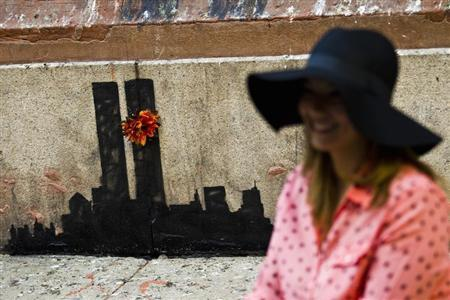 A woman poses for a picture next to new artwork by British graffiti artist Banksy at Lower Manhattan in New York