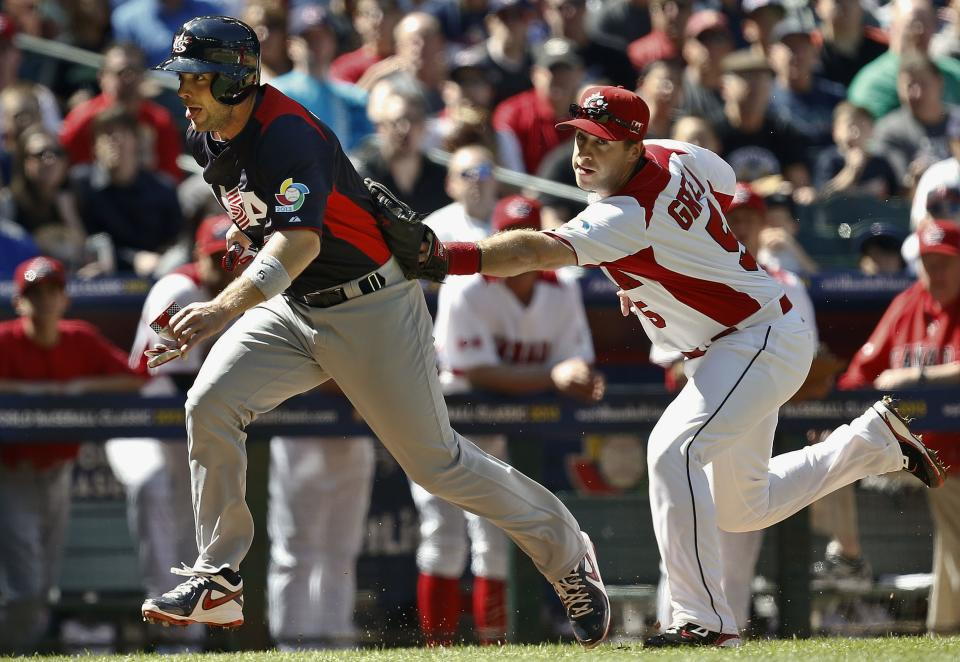 United States' David Wright, left, gets tagged out during a rundown by Canada's Taylor Green as Wright tries to score a run in the second inning during a World Baseball Classic baseball game on Sunday, March 10, 2013, in Phoenix. (AP Photo/Ross D. Franklin)