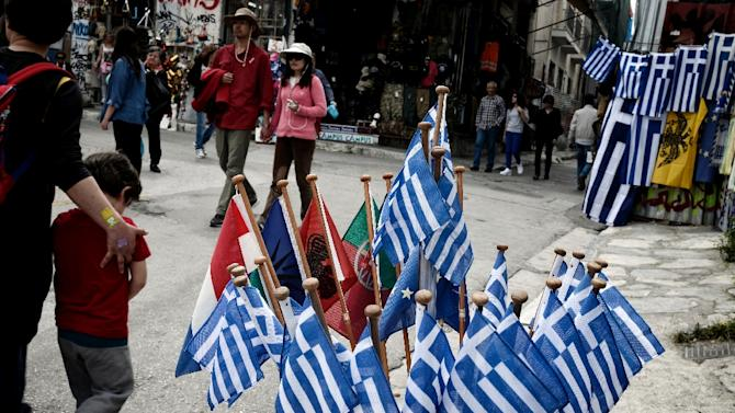 People walk past Greek flags for sale in central Athens on April 18, 2015
