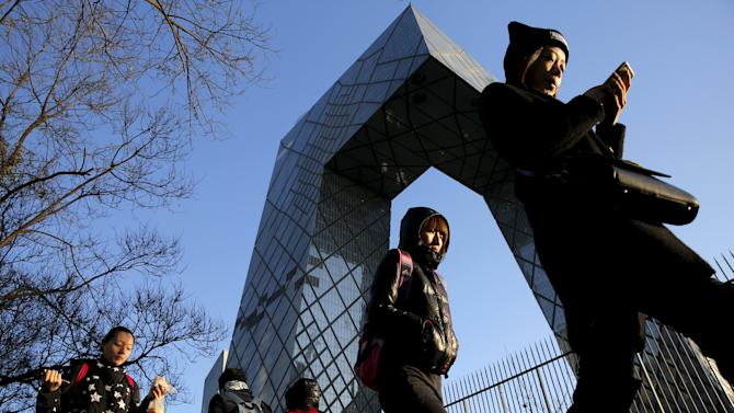 Morning commuters walk in front of the CCTV building on a sunny day with no pollution in Beijing