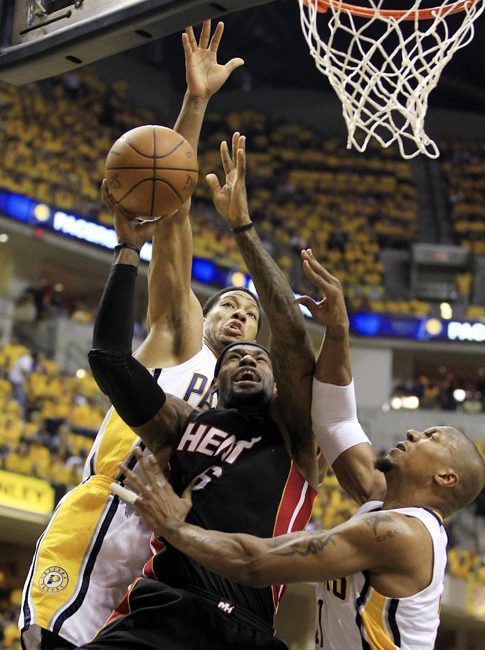 Miami Heat's LeBron James, center, shoots against Indiana Pacers' Danny Granger, left, and David West, right, during the first half of Game 6 of their NBA basketball Eastern Conference semifinal playoff series, Thursday, May 24, 2012, in Indianapolis. (AP Photo/Darron Cummings)