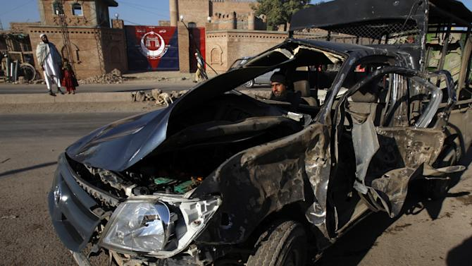 A Pakistani police officer inspects a vehicle damaged in a blast on Monday, Dec. 3, 2012 in Peshawar, Pakistan. A bomb ripped through a police van as it was patrolling in northwestern Pakistan on Monday, killing several officers and wounding others, police said. (AP Photo/Mohammad Sajjad)