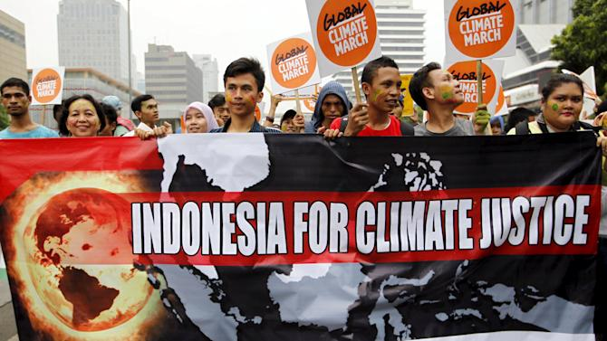 People hold placards and banners as they participate in a march ahead of the Paris World Climate Change Conference in Jakarta