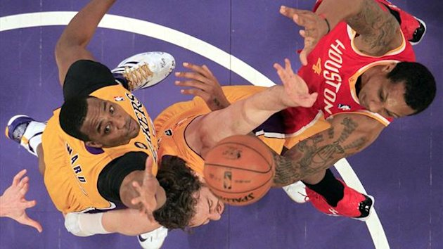 Los Angeles Lakers Dwight Howard (L) and Pau Gasol of Spain (C) fight for a rebound with Houston Rockets Greg Smith during their NBA basketball game in Los Angeles