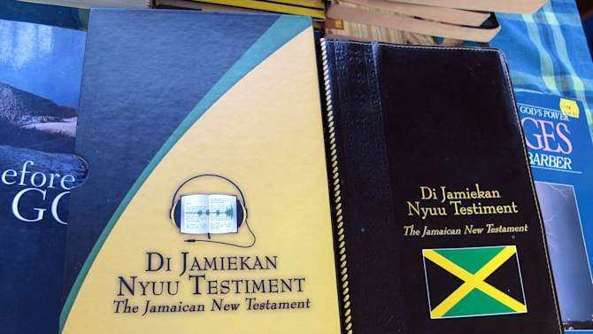 "In this Dec. 3, 2012 photo, the covers of two editions of the new Jamaican patois translation of the New Testament are shown at the office of the Bible Society of the West Indies in Kingston, Jamaica. After years of translation from the original Greek, the Bible Society is releasing in Jamaica print and audio CD versions of the first patois translation of the New Testament, or ""Di Jamiekan Nyuu Testiment."" The language was created by slaves who were brought to the island by European colonizers, and some say it was designed to prevent slave masters from understanding their words. (AP Photo/David McFadden)"