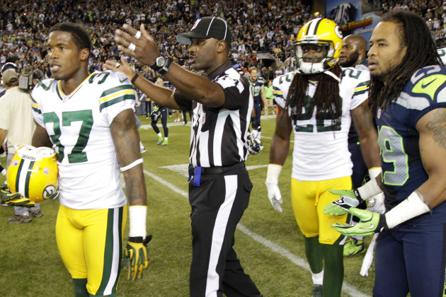 An official gestures as Green Bay Packers cornerback Sam Shields (37), safety Jerron McMillian (22) and Seattle Seahawks free safety Earl Thomas (29) leave the field in the second half of an NFL footb