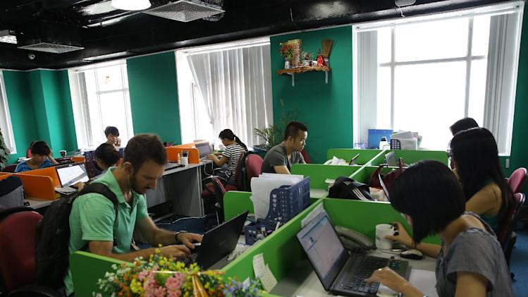 Staff work at a newly launched Russian- Vietnamese web company which is developing its search engine, Coc Coc to compete with Google for the local market in Ha Noi, Viet NamWednesday, May 14, 2013. The company has so far spent $10 million, hired 300 staff _ included 30 foreigners, mostly Russians and according to founders, its investors have $100 million over the next five years to try and get a chunk of the 97 percent of Vietnamese web surfers who currently use Google to switch. (AP Photo/Na Son Nguyen).