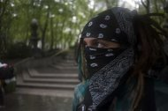A masked demonstrator with the Occupy Wall Street movement waits to take part in a general strike in New York