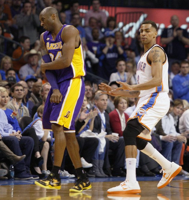 Los Angeles Lakers guard Bryant holds his right elbow as Oklahoma City Thunder forward Sefolosha looks on in the first half of their NBA basketball game in Oklahoma City.