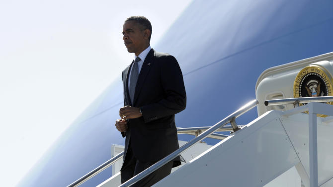 """President Barack Obama walks down the steps of Air Force One after arriving at Southwest Florida International Airport in Ft. Myers, Fla., Friday, July 20, 2012. Obama is cutting short a Florida campaign swing following the deadly Colorado movie theater shooting. He called the shooting """"horrific"""". (AP Photo/Susan Walsh)"""