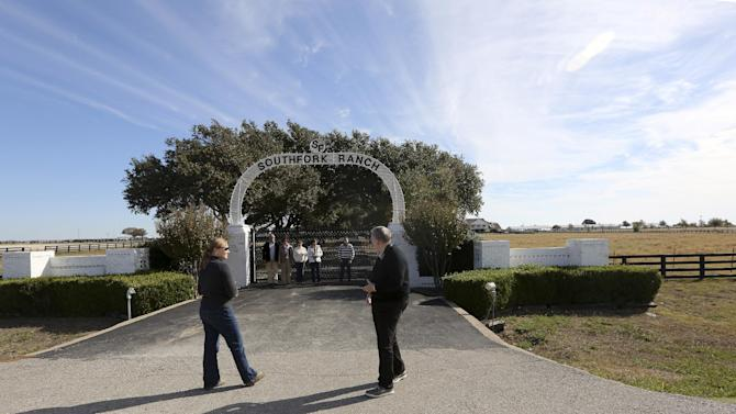 "In this photo made Tuesday, Nov. 13, 2012, tourists line up fore a photo at the front gate of Southfork Ranch in Parker, Texas. Tourists have been flocking to Southfork Ranch since the early years of the classic series, which ran from 1978 to 1991. And a new ""Dallas"" starting its second season on TNT on Monday and the recent death of the show's star, Larry Hagman, who legendarily played conniving Texas oilman J.R. Ewing, have also spurred fans to visit. (AP Photo/LM Otero)"