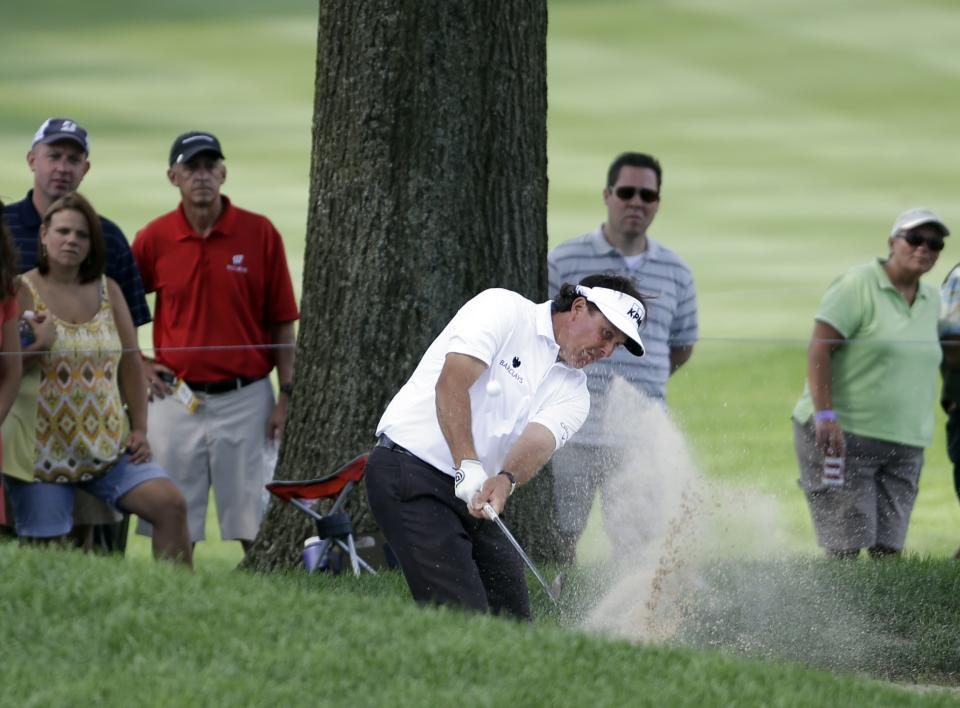 Phil Mickelson hits from a fairway bunker to the 10th hole during the first round of the Bridgestone Invitational golf tournament Thursday, Aug. 1, 2013 at Firestone Country Club in Akron, Ohio. (AP Photo/Mark Duncan)