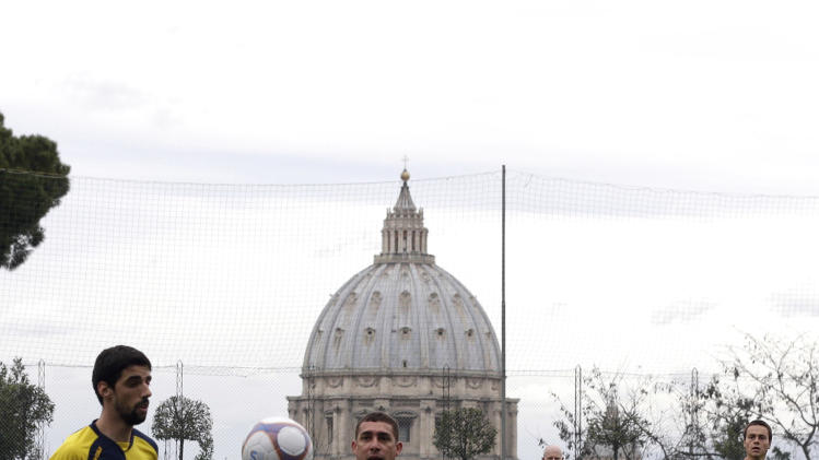 "Players of Redemptoris Mater and Collegio Pio Brasiliano teams play their Clericus Cup soccer match in Rome, Sunday, March 10, 2013. Vatican-supported soccer league matches went ahead as scheduled Sunday on a hill overlooking St. Peter's Basilica, shown in background. For the teams of seminaries, missionaries and oratories, however, the pre- and post-game talk centered on the coming conclave to elect a new pope. A coach of a Brazilian team was absent because he was chosen to drive two cardinals to Assisi for the day. ""It didn't go so well today,"" Aldemir Fracisco Belever, the captain of the Collegio Pio Brasiliano seminary said after a 4-1 loss to Redemptoris Mater, a team featuring seminarians and priests with the Mater neocatechumenal movement. ""It wasn't easy without our coach."" (AP Photo/Alessandra Tarantino)"
